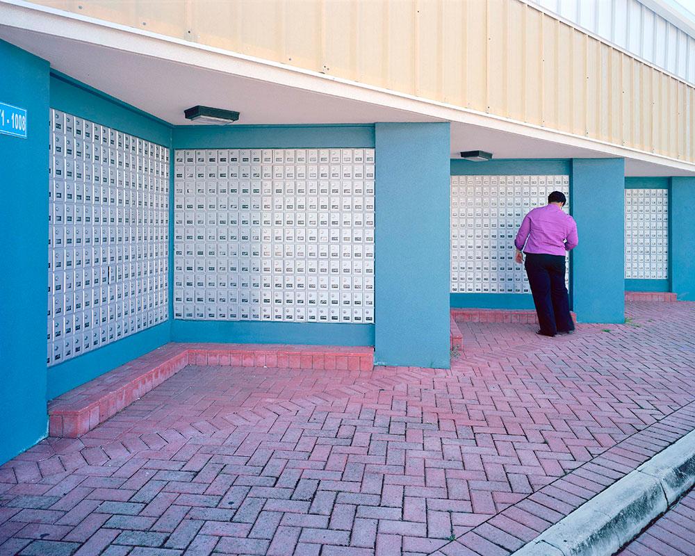 Un uomo apre la sua cassetta delle lettere nelle Isole Cayman