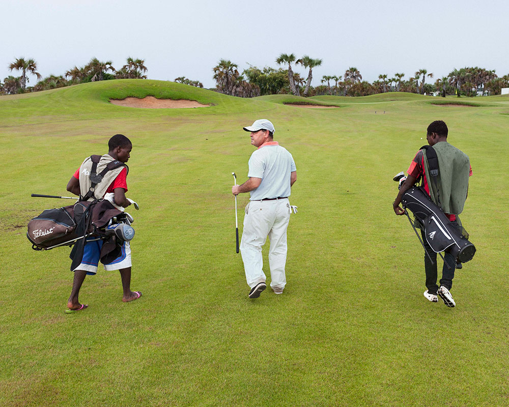 A golfer at Mangais golf course near Luanda, Angola. From The Heavens 2015 © Paolo Woods & Gabriele Galimberti
