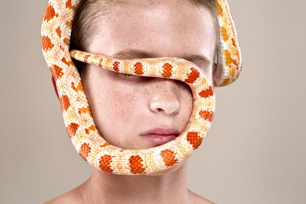 studio portrait of a boy with his pet snake