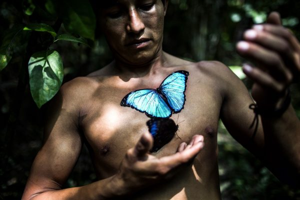 Portrait image by of a man and a butterfly in Peru, South America. Photograph by Javier Arcenillas