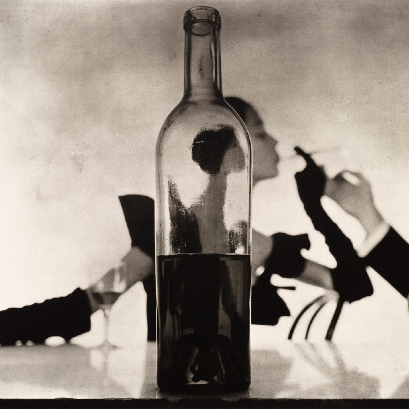 black and white portrait of a woman through a glass bottle