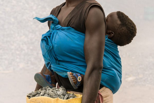 Portrait of a woman with her child is working in a quarry in Uganda