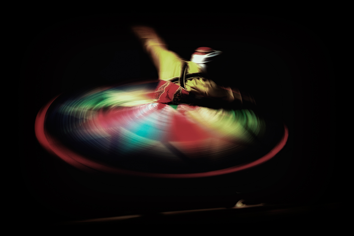 Dervish Splendor - a man in colorful clothes in dancing