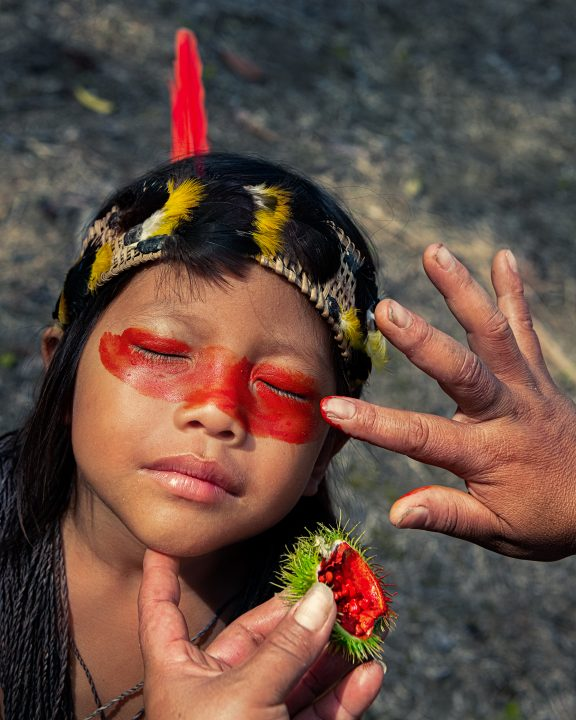 young Waorani girl receiving colorful make up by her grandmother in the ecuadorian amazon