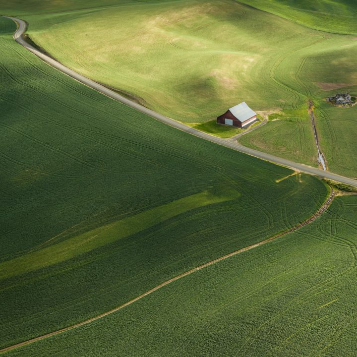 Colorful Aerial photograph of a lone barn along a quiet road in the Palouse region of Washington State, USA