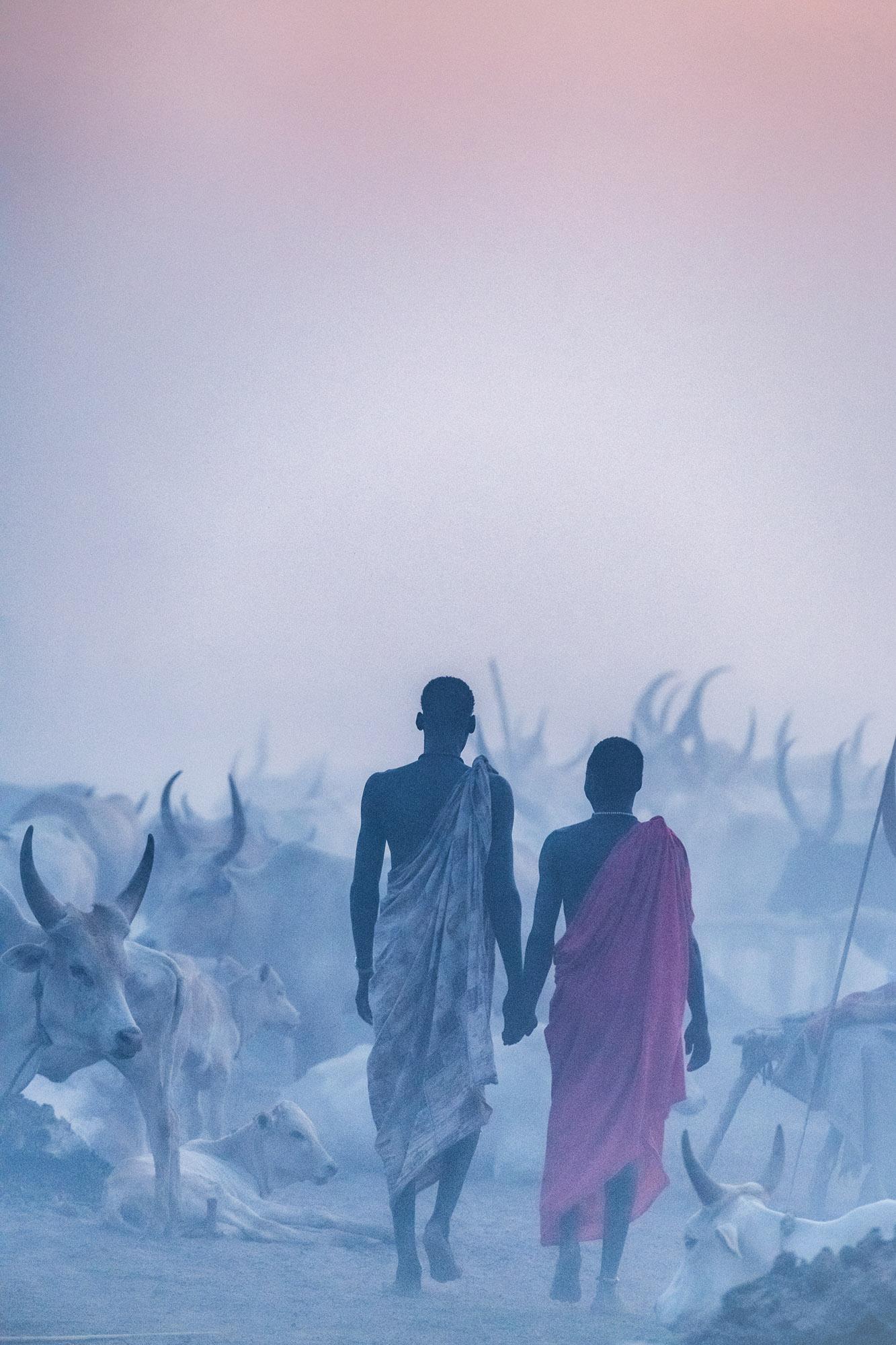 Photographie de voyage par Trevor Cole de deux hommes entourés de leur bétail marchant à Khartoum, Soudan