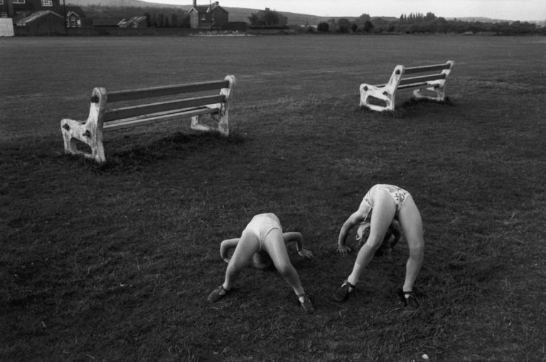 Black and white street photography by Richard Kalvar of kids playing in the grass. Shot in New York, Long Island