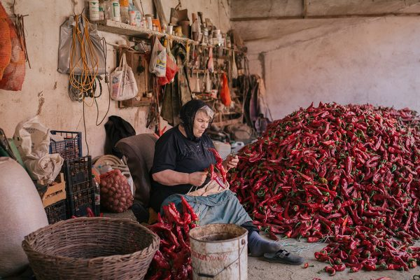 An elderly woman prepares threads of red paprika on September 19, 2020 in Donja Lokosnica, Serbia