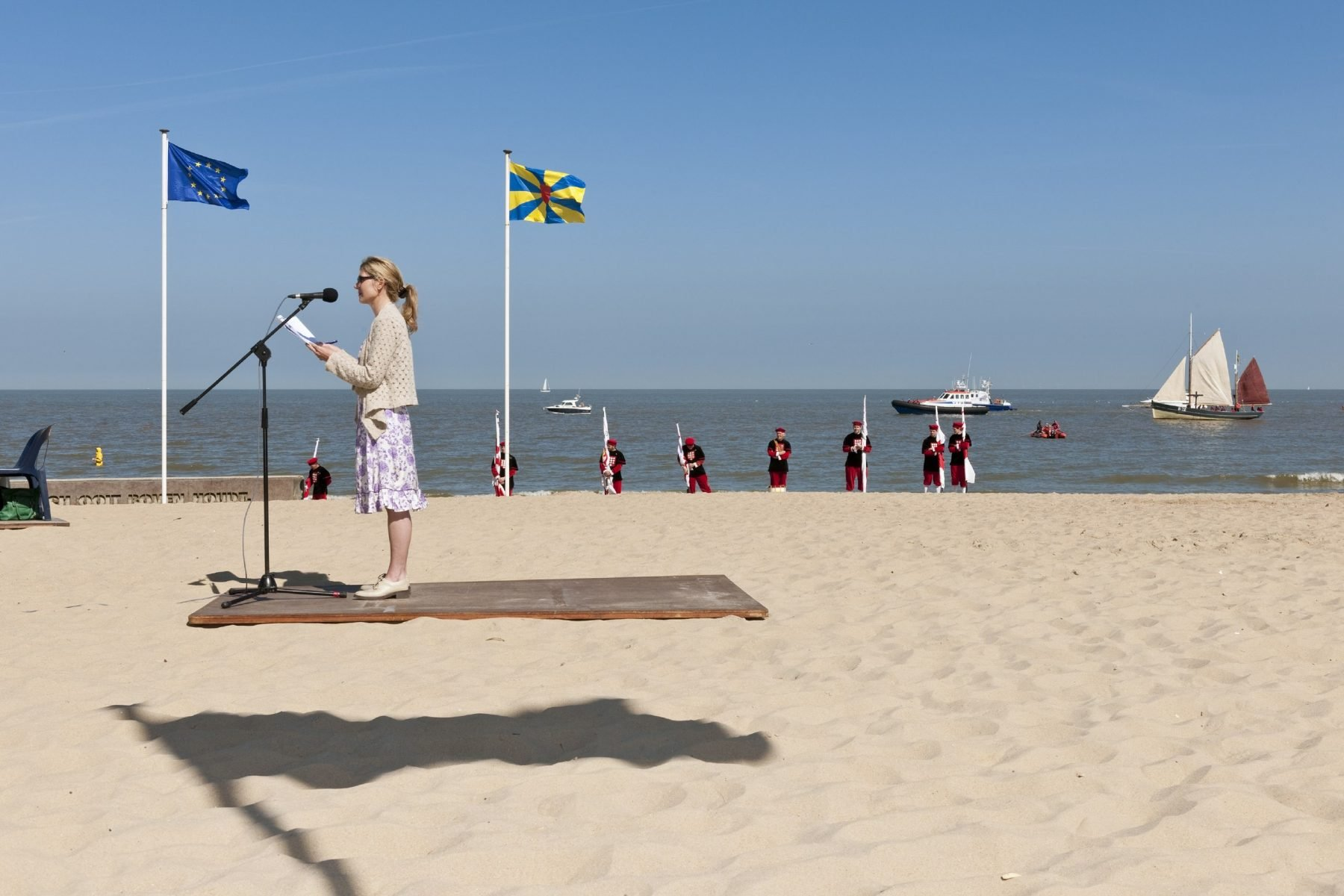 Color street photograph of women giving speech on beach with flags by Nick Hannes