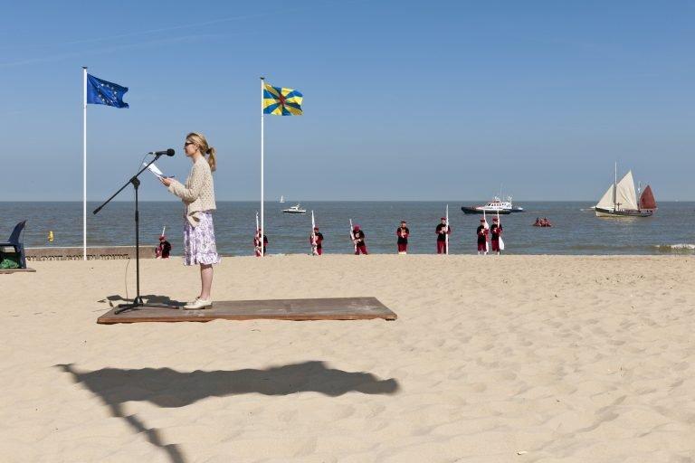 Photographie de rue couleur de femmes donnant un discours sur la plage avec des drapeaux par Nick Hannes