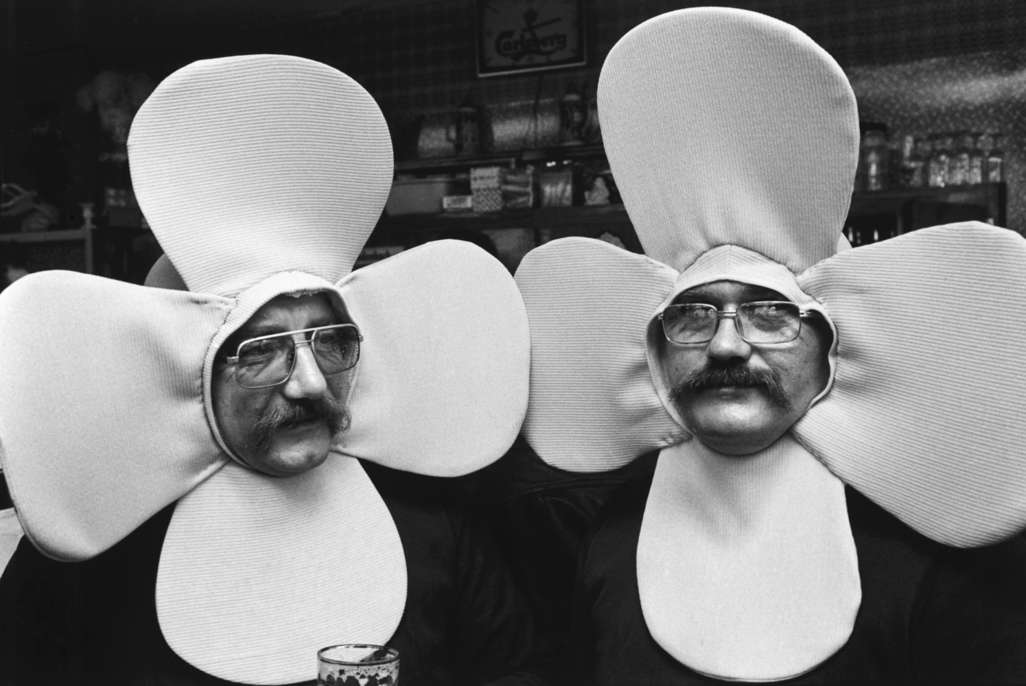 Black and white street photography by Richard Kalvar, two men dressed as flowers in La Louviere, Belgium.