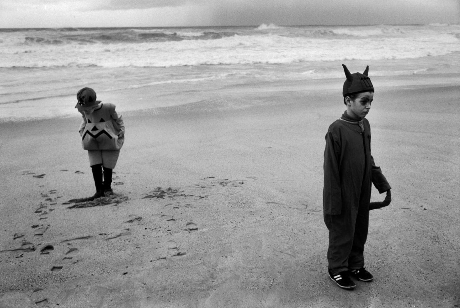 Black and white street photography by Richard Kalvar, two children in fancy dress on the beach in Biarritz, France.