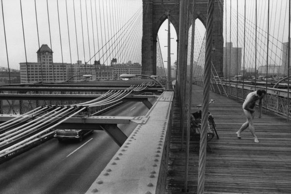 Black and white street photography by Richard Kalvar, nude man on Brooklyn Bridge