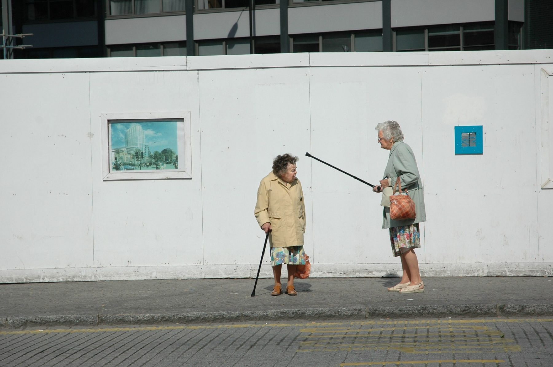 Color street photograph of elderly women arguing by Paul Russell