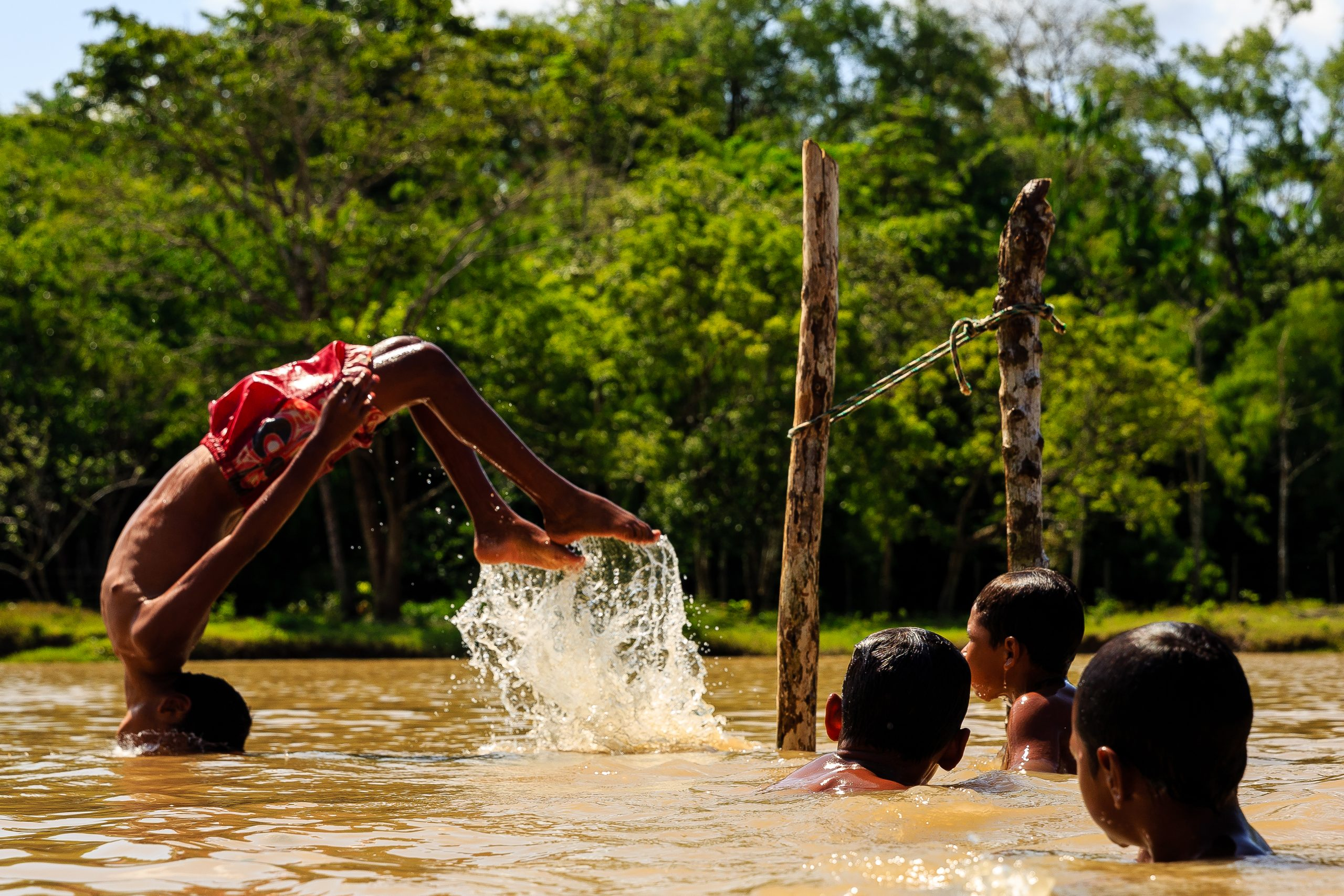 Color photo by Diego Baravelli of boys swimming in a river, Brazil