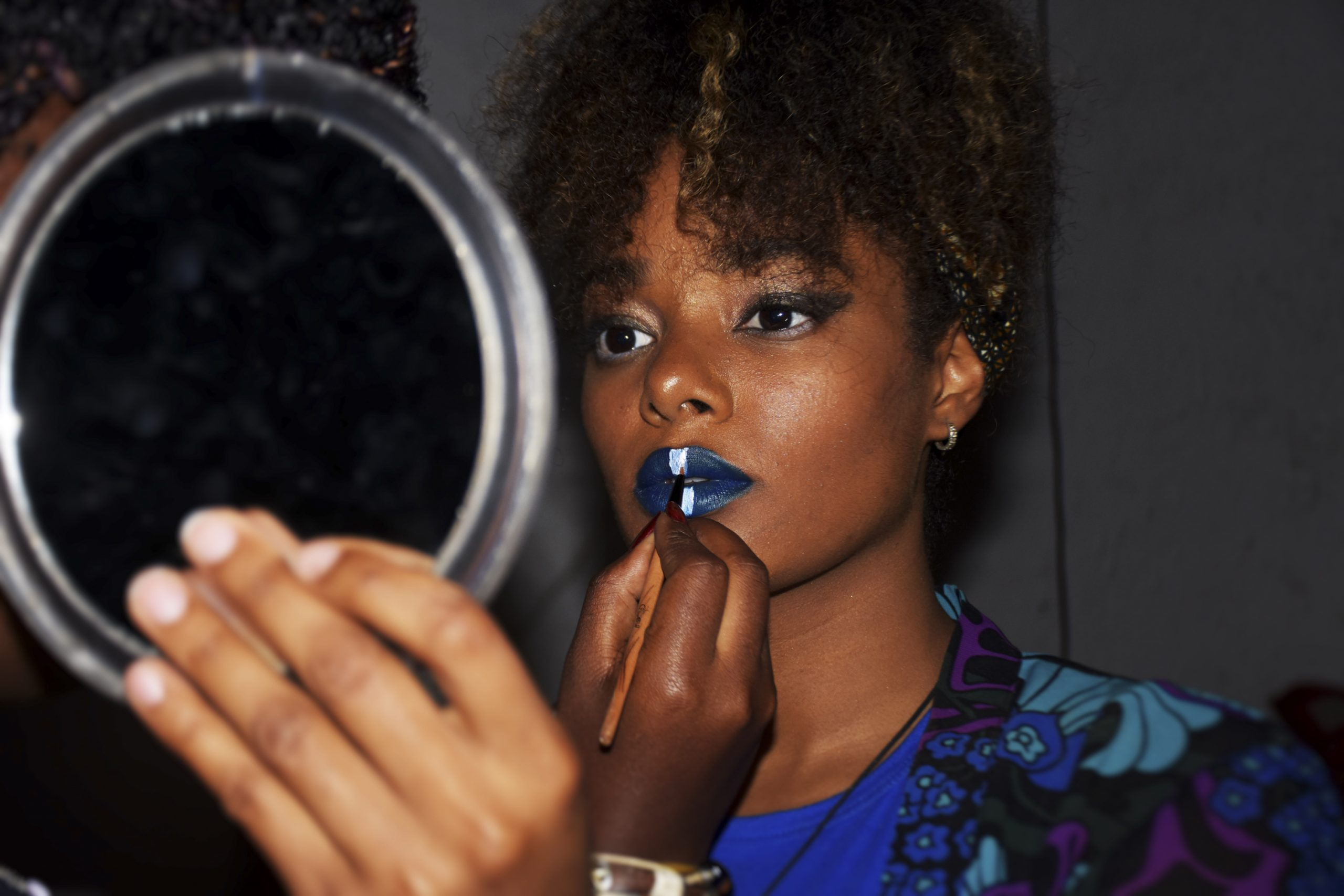Color photo by Ley Uwera of women applying make up at Goma fashion week, Democratic Republic of the Congo