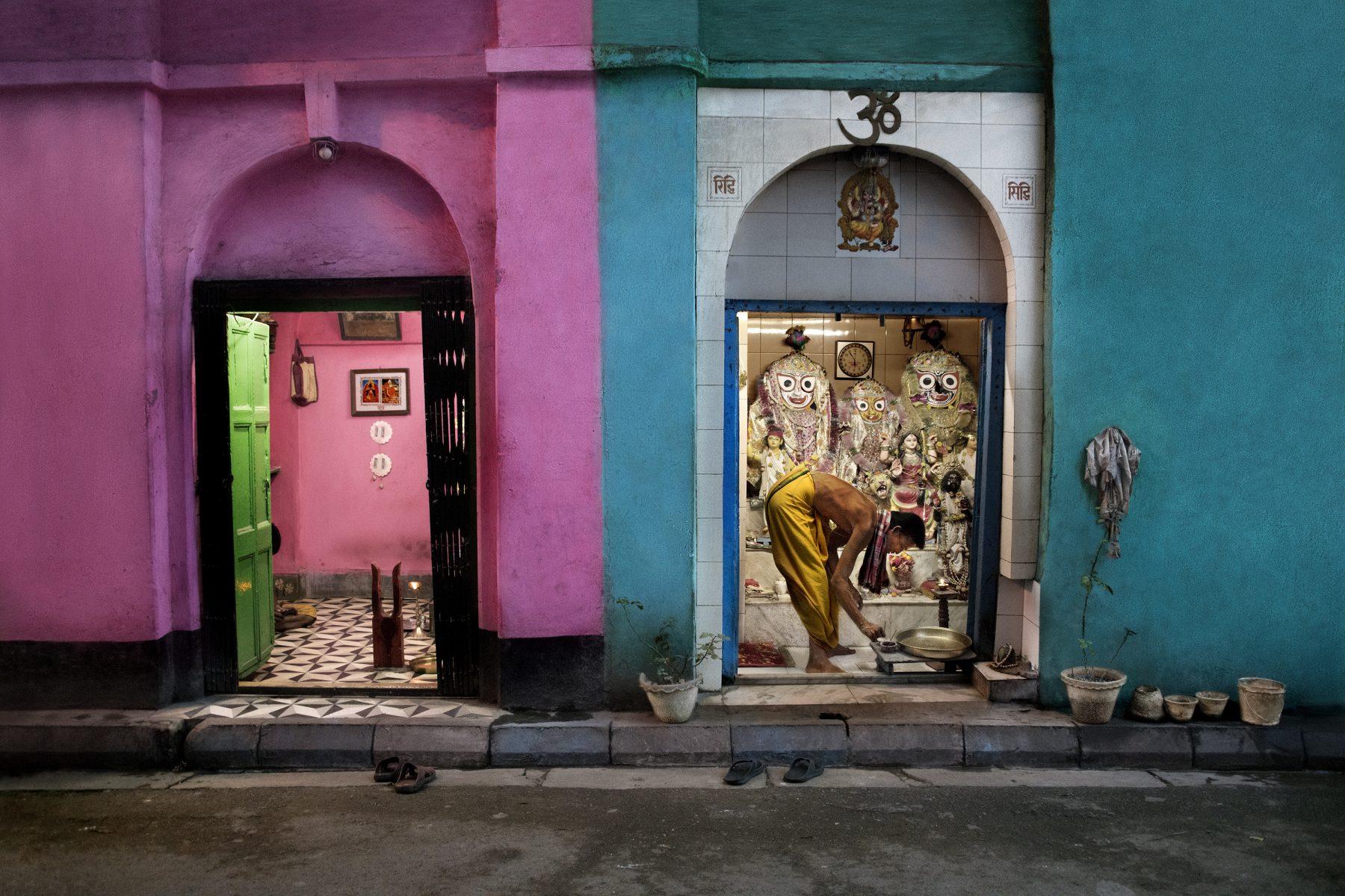 Photographie couleur par Steve McCurry, Inde, maisons colorées, homme se baignant, Kolkata