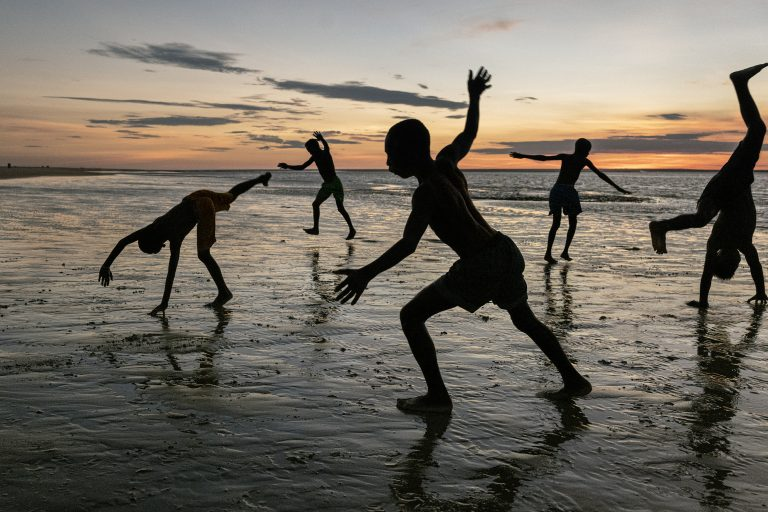 Color photograph by Steve McCurry, Madagascar, boys playing on beach, sunset, sillouhettes
