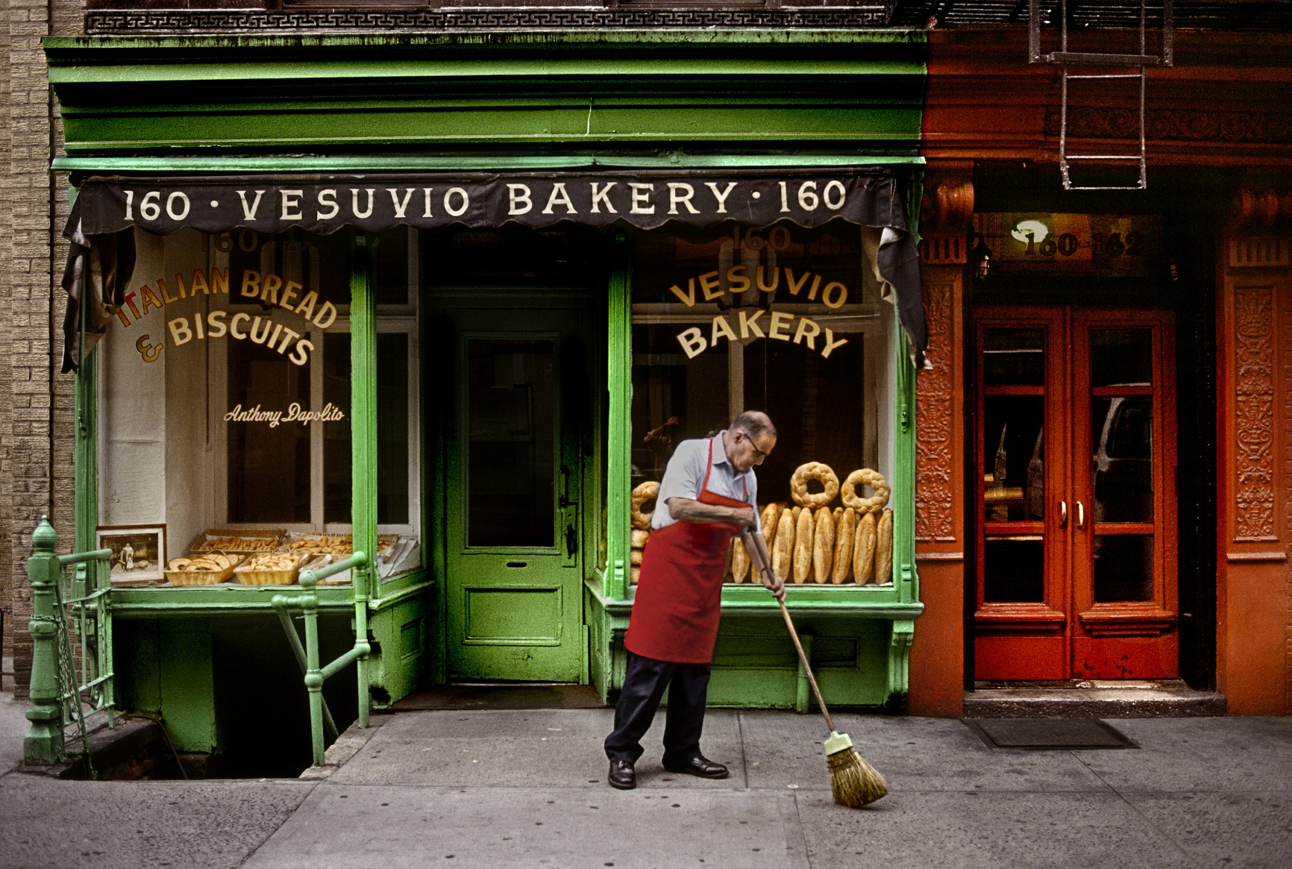Color photograph by Steve McCurry, NYC, USA, man sweeping up on the street outside Italian bakery.
