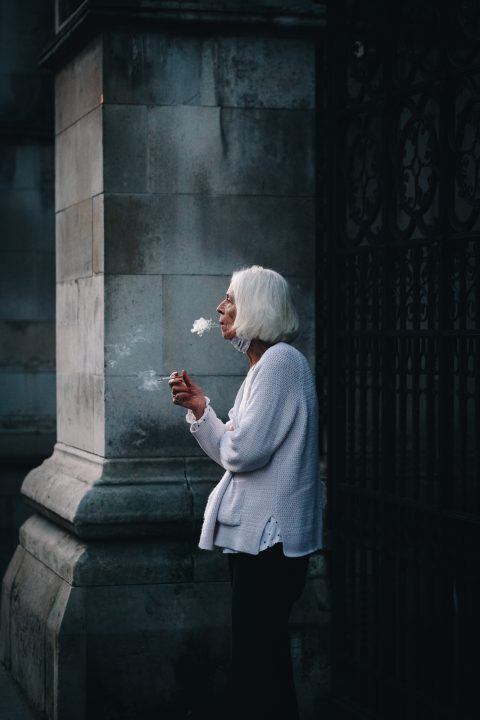 Candid portrait of a woman smoking in the streets of Holborn, London, UK 2020