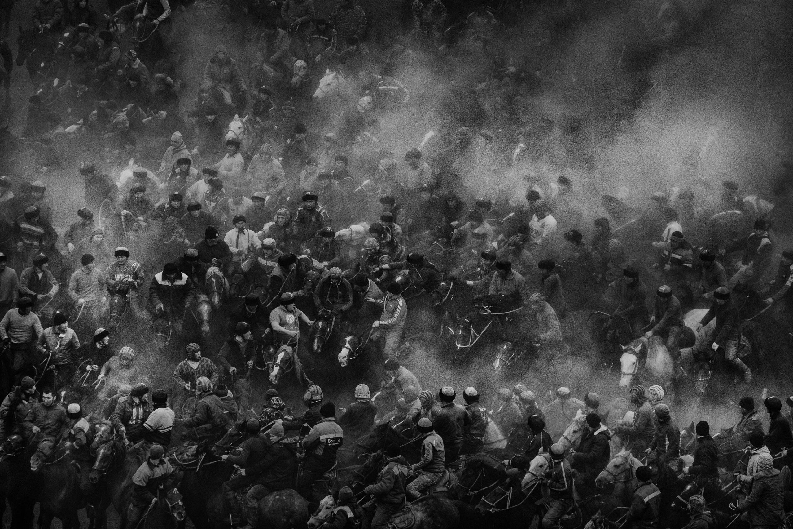fotografia in bianco e nero di Alain Schroeder scattata Nel villaggio di Uzgen, Kirghizistan, dove più di 170 cavalli e uomini giocano a Kok Boru.