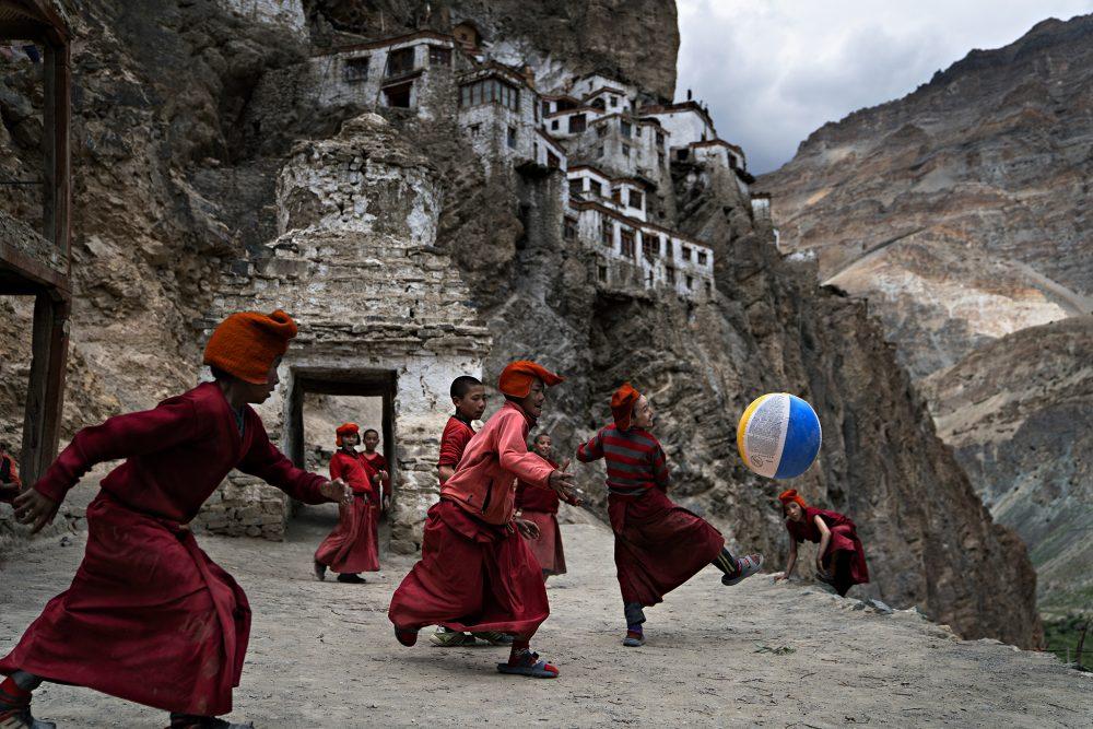 Photographie couleur de jeunes moines tibétains jouant au football dans le monastère de Phugtal, dans le nord de l'Inde