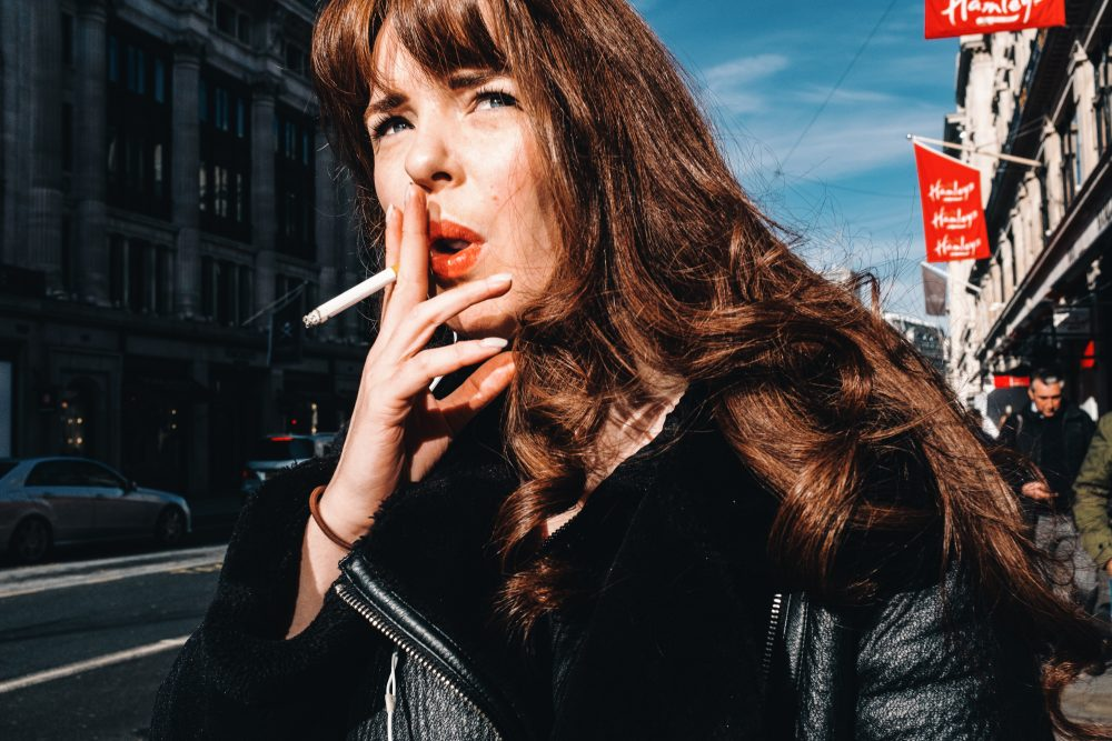 Portrait photograph of a woman with red lipstick and blue eyes in Oxford Street, London, UK by Francesco Gioia