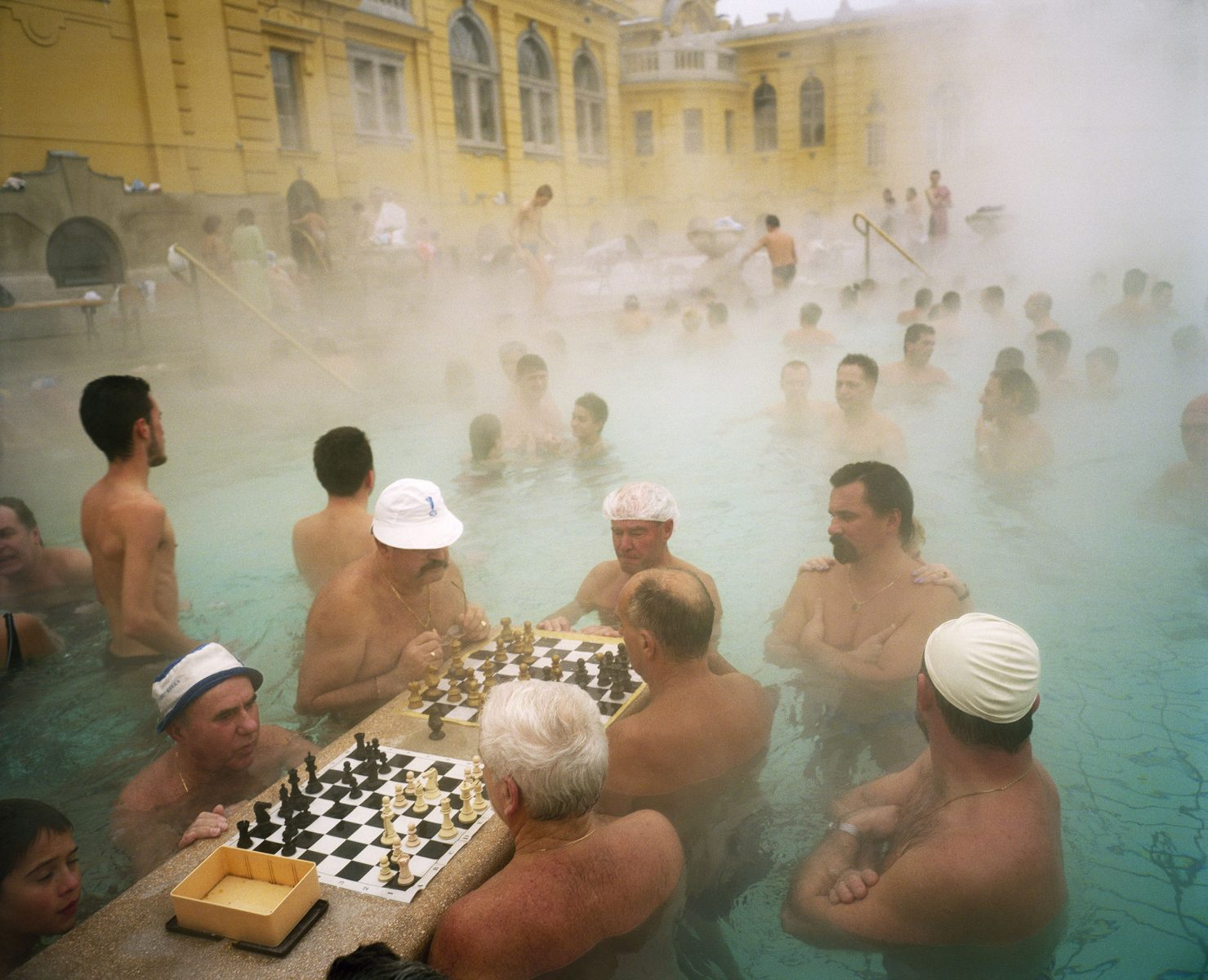 Color photo by Martin Parr men bathing and playing chess at Szechenyi Thermal Baths, Budapest, Hungary, 1997