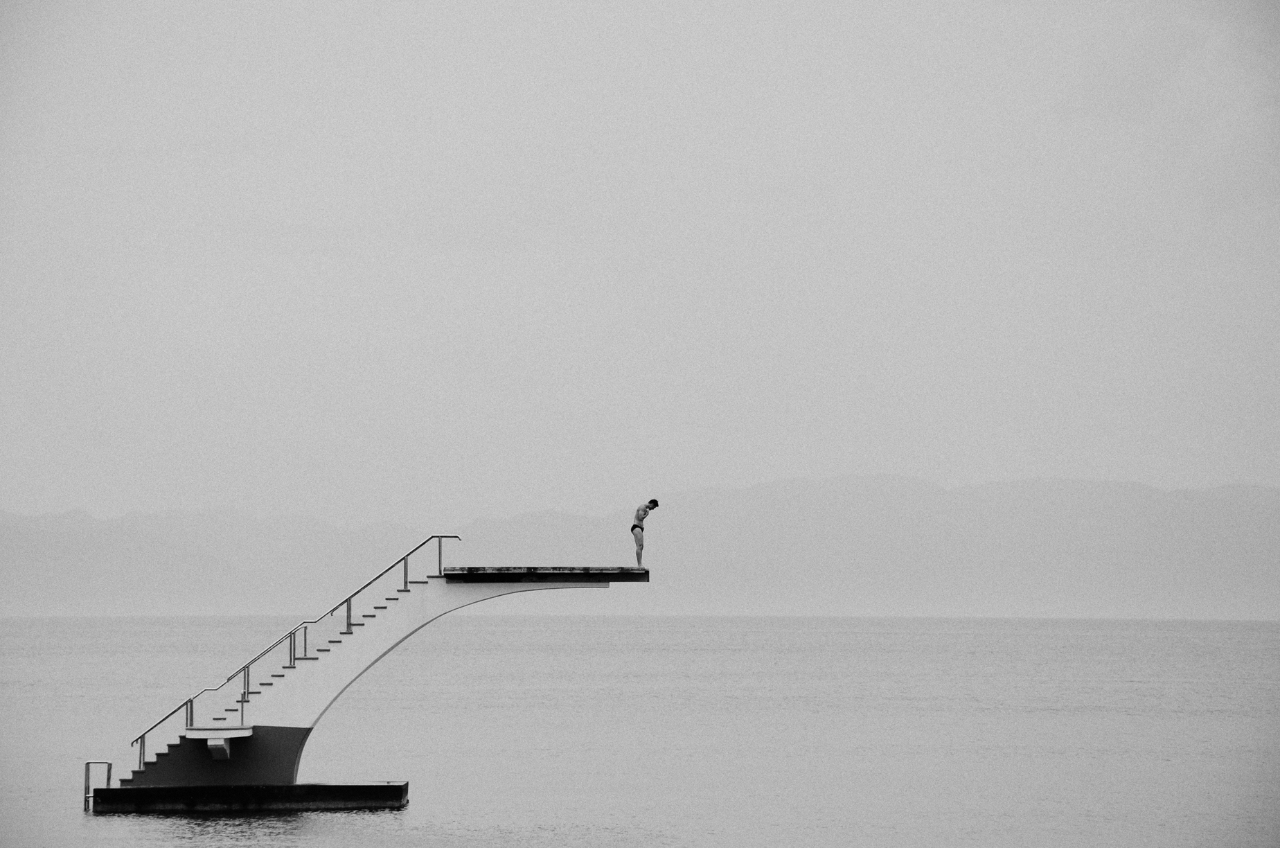 Open Call - black and white photograph of a man diving in the sea in Rhodes, Greece