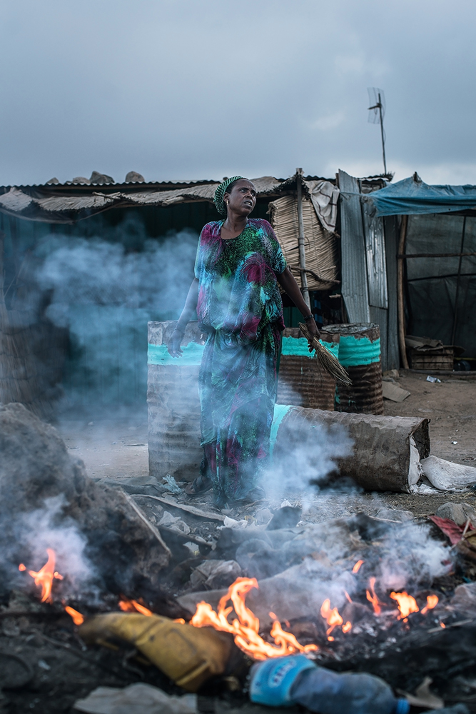 Color photograph by Nichole Sobecki, woman, fire, Djibouti, Africa