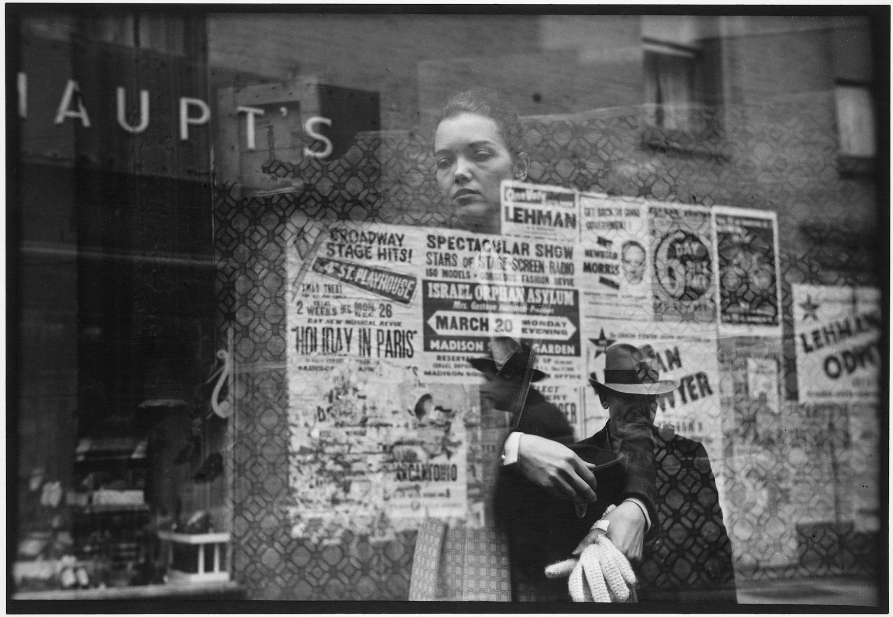 Photo en noir et blanc de Saul Leiter, femme regardant à travers la fenêtre, des affiches, des reflets