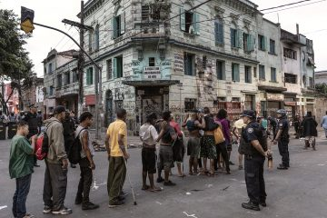 Foto a colori di Gui Christ dalla sua serie Fissua. gli uomini si mettono in fila durante un raid della polizia nel più grande mercato di droga all'aperto del mondo, San Paolo, Brasile