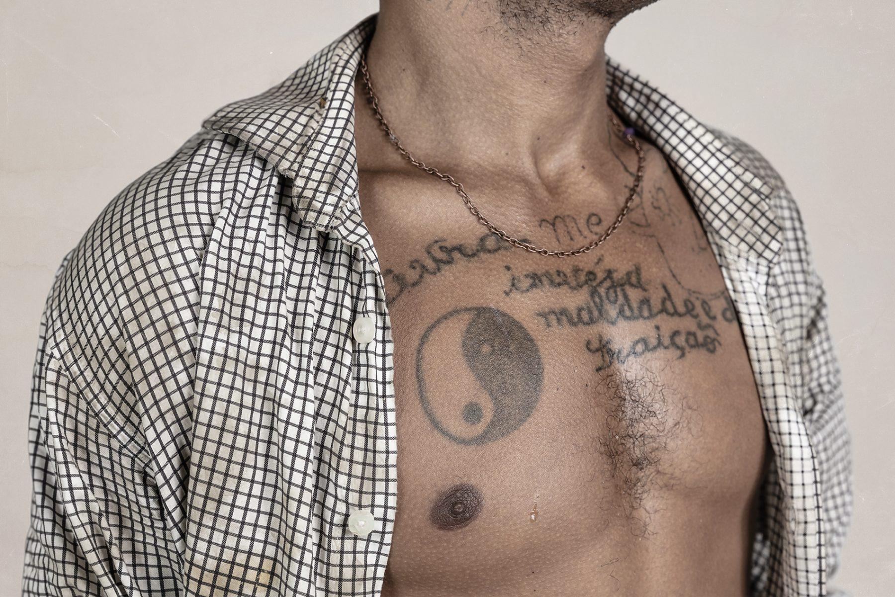 Fotografía en color de Gui Christ de su serie Fissura. hombre con camisa abierta, pecho, tatuajes, São Paulo
