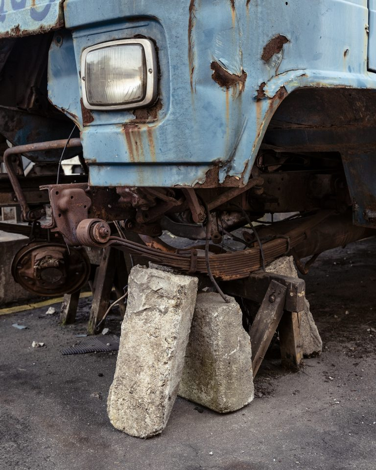 Fotografía en color de Gui Christ: camión azul con ruedas faltantes, sobre ladrillos.