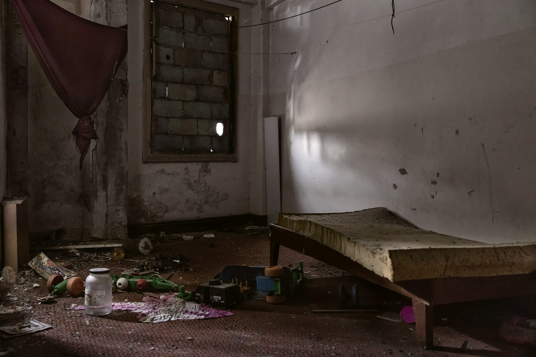 Photo couleur par Gui Christ, pièce abandonnée, attirail de drogue, matelas sale, poubelle