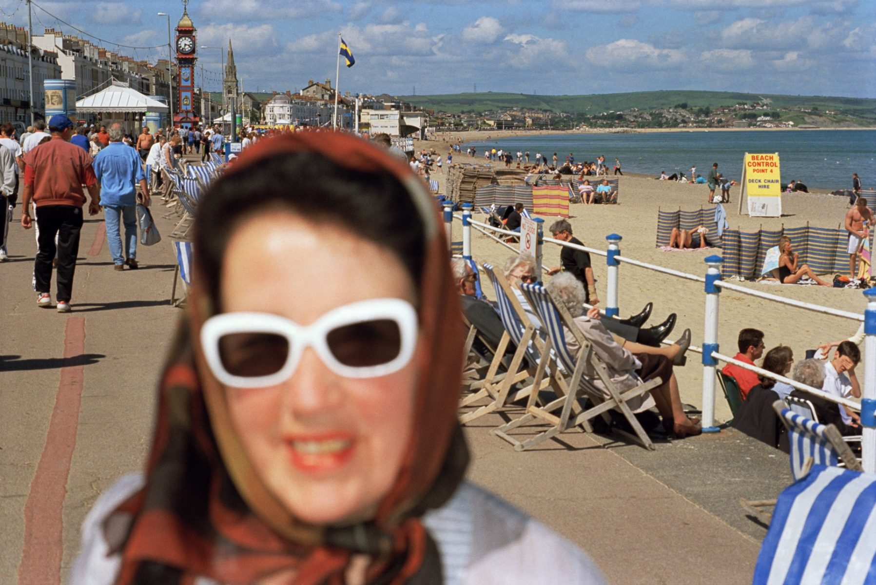 Color photo by Martin Parr, woman in sunglasses on promenade, with beach and tourists in the background. Weymouth England