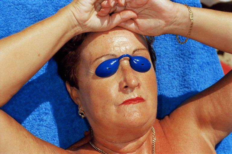 Photo couleur par femme Martin Parr, bronzer dans des lunettes de soleil bleues avec une serviette bleue, Benidorm Espagne.