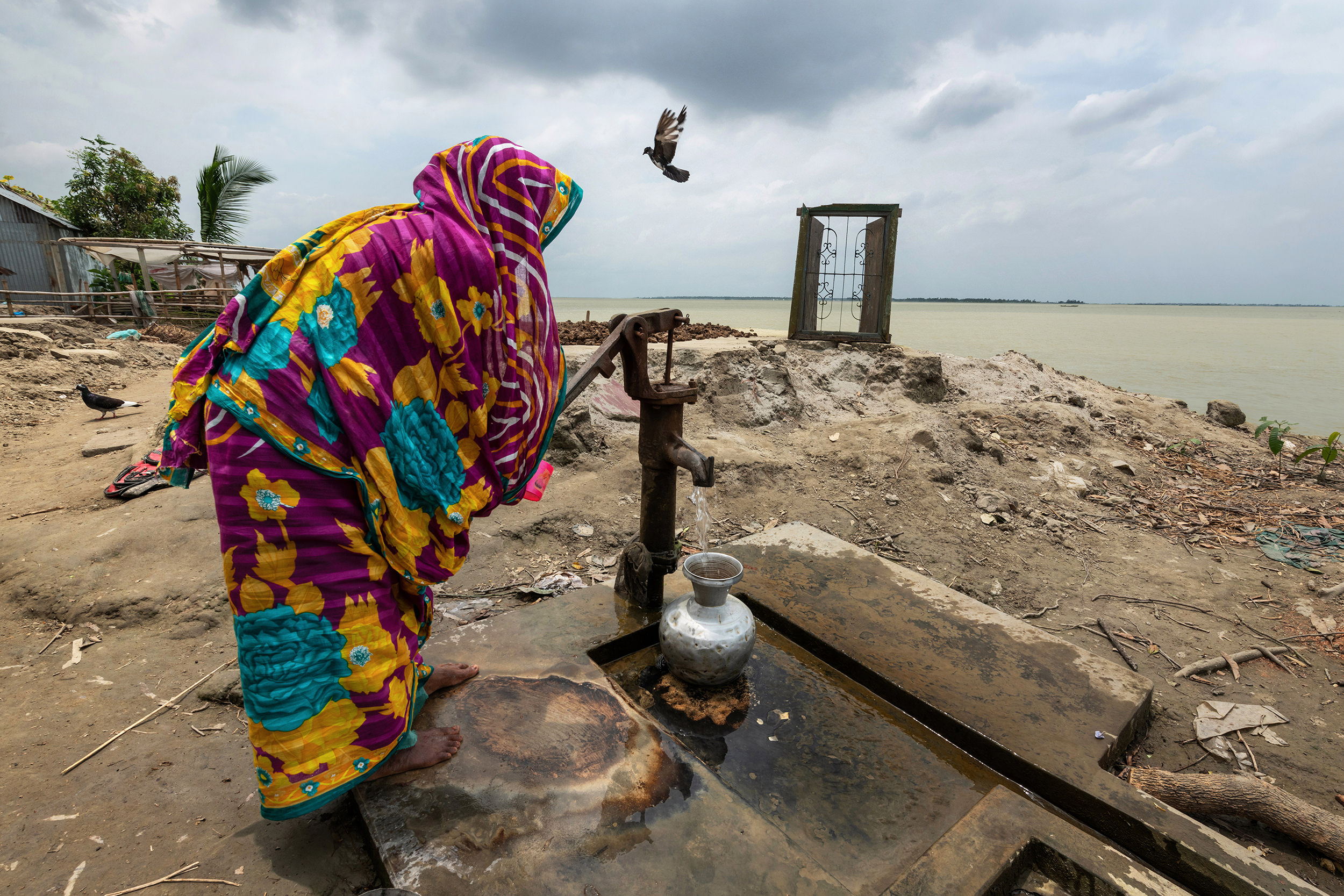 Color photograph of a woman collecting water on eroded land in Bangladesh - Visual Storytelling Award
