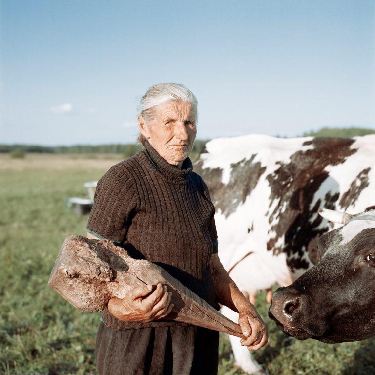 Portrait photographique couleur par Tadas Kazakevičius, à partir de Soon to be Gone femme, tenue, bâton, vache, champ