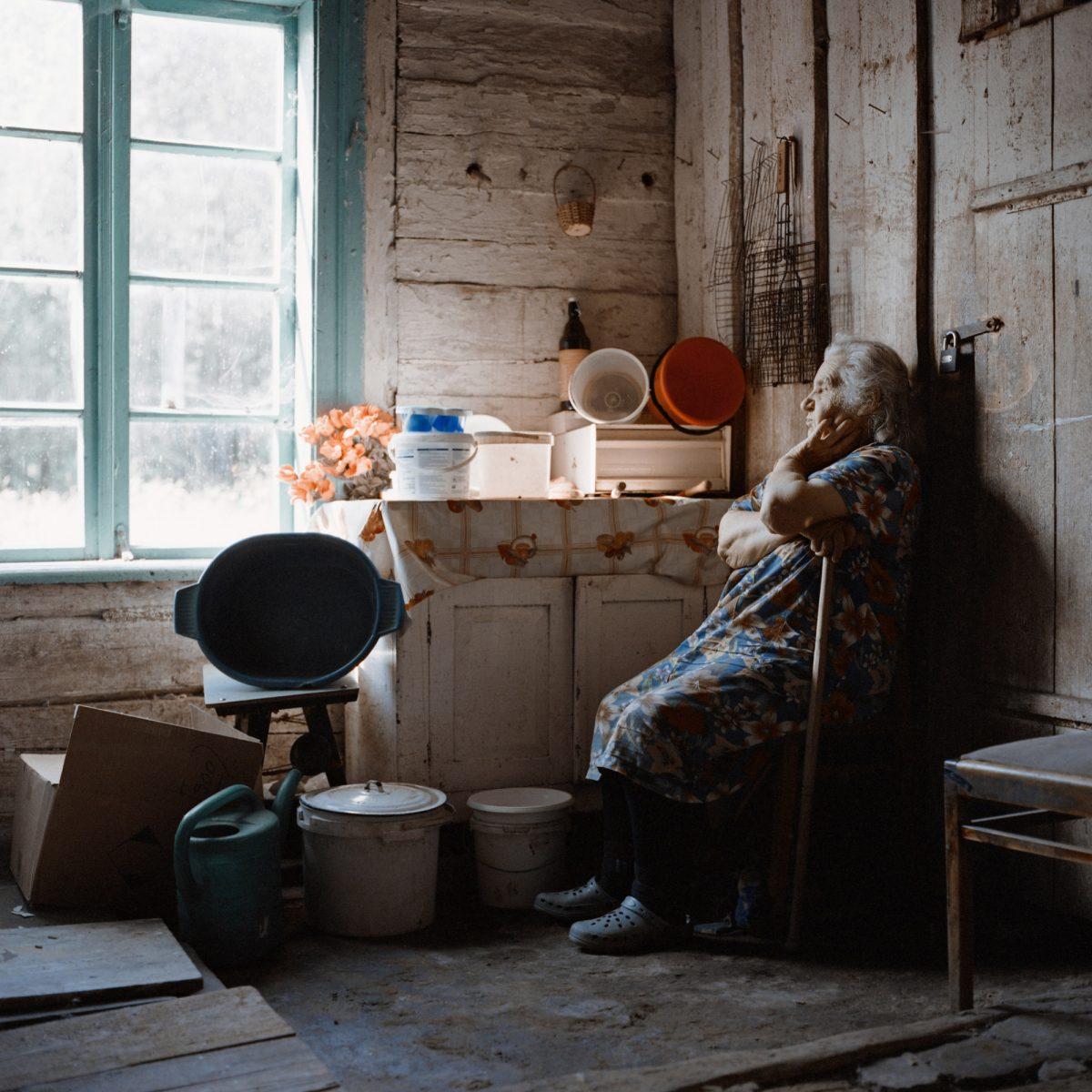 Photo couleur de Tadas Kazakevičius de Soon to be Gone, femme âgée dans la maison regardant par la fenêtre.