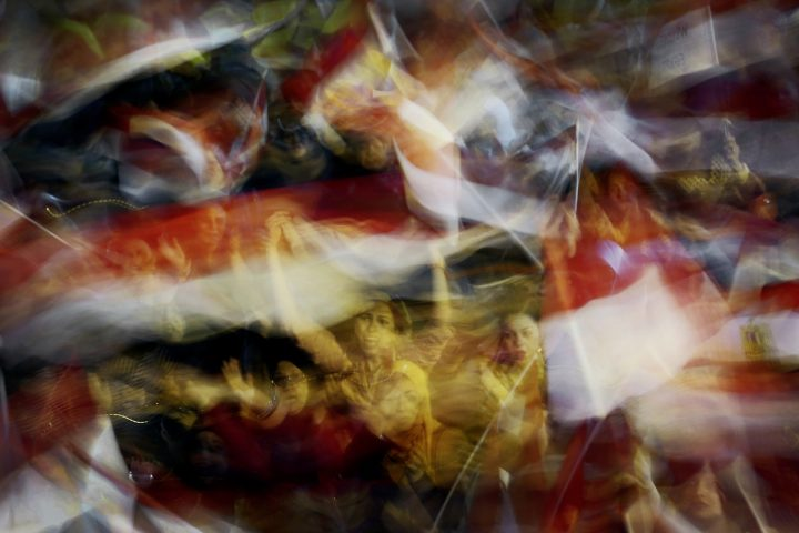 Color photo by Laura El-Tantawy from IN THE SHADOW OF THE PYRAMIDS. Women waving flags.Tahir Square, Cairo, Egypt, Revolution