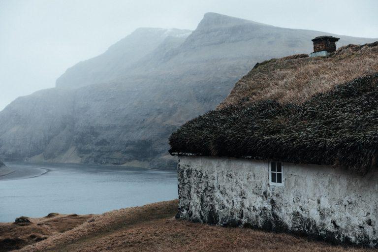 Photo de paysage de Hannes Becker. Maison au toit d'herbe, montagnes, îles Féroé.