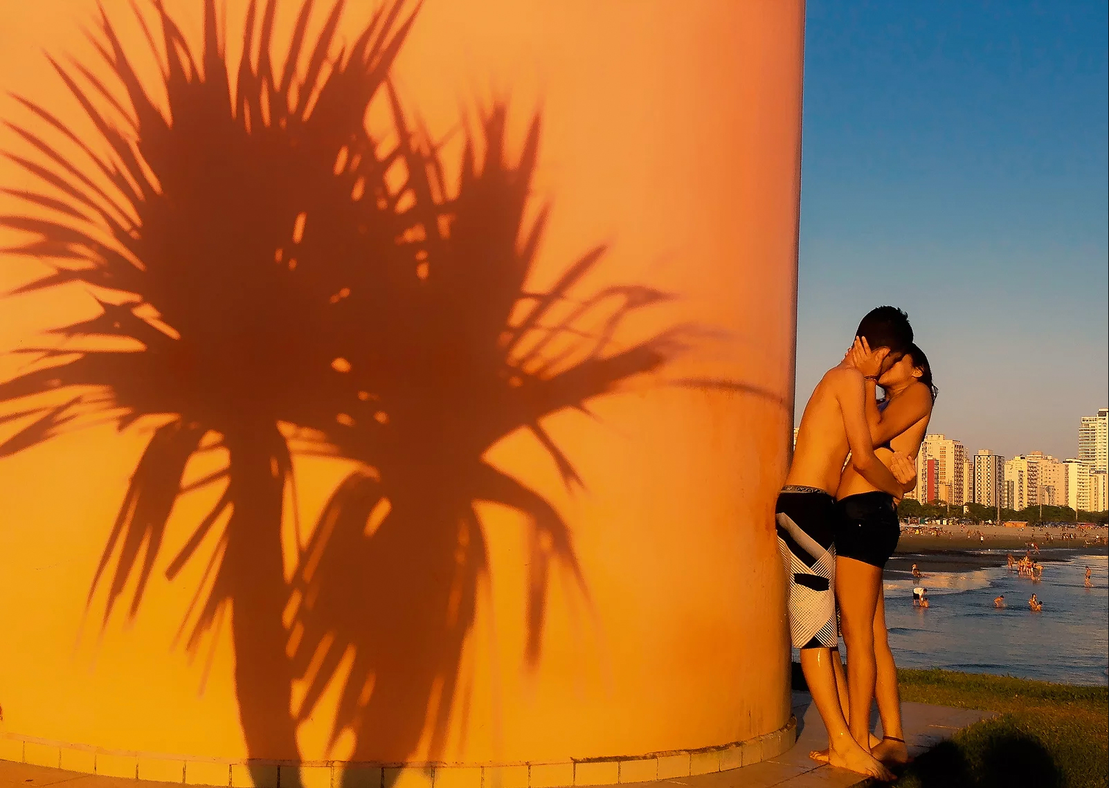 color photo by Alex Almeida from Brazil Tropical light. young couple embrace, kissing