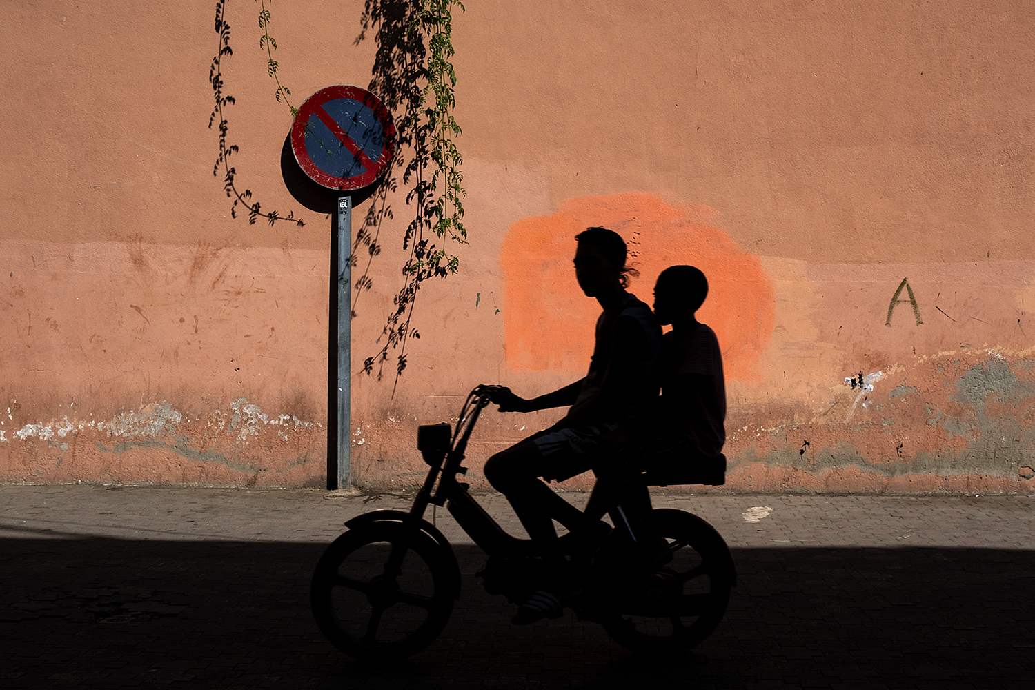 color street photography award of two boys shadow on a motorbike in Morocco by Costas Delhas
