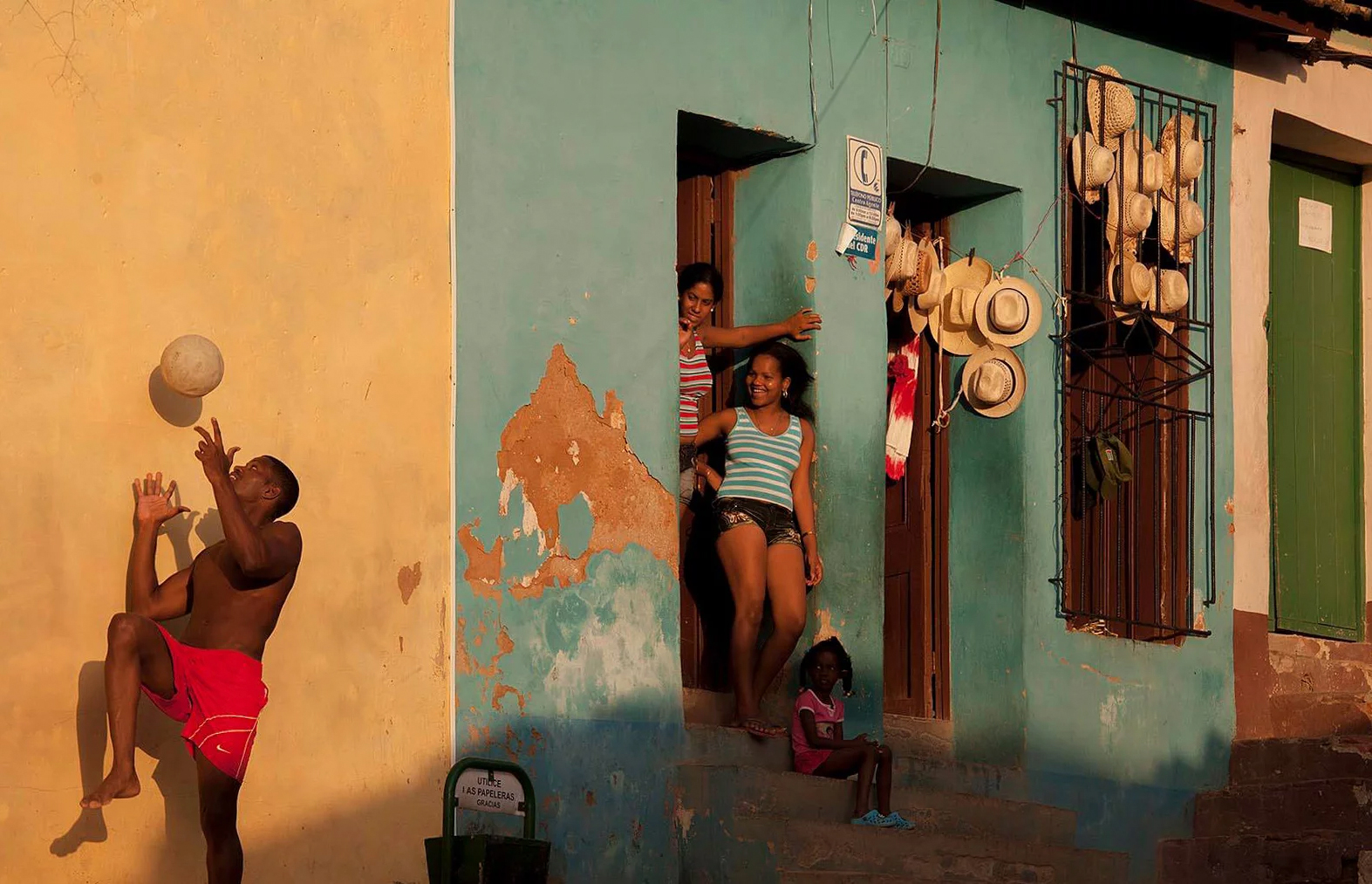 Color photo by Alex Almeida, family, guy playing soccer Cuba.