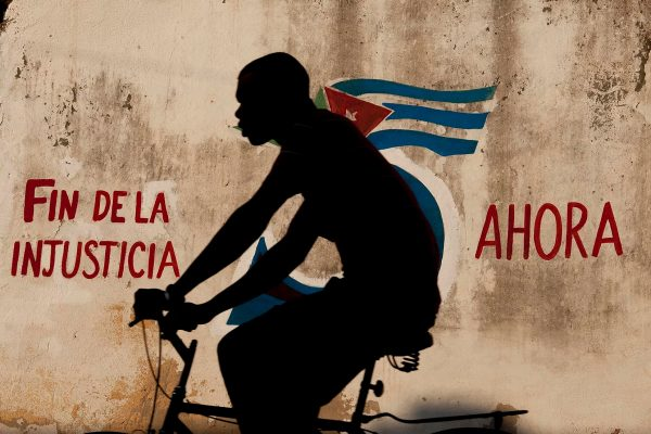 Color photo by Alex Almeida, boy cycling in front of cuban flag mural Cuba.