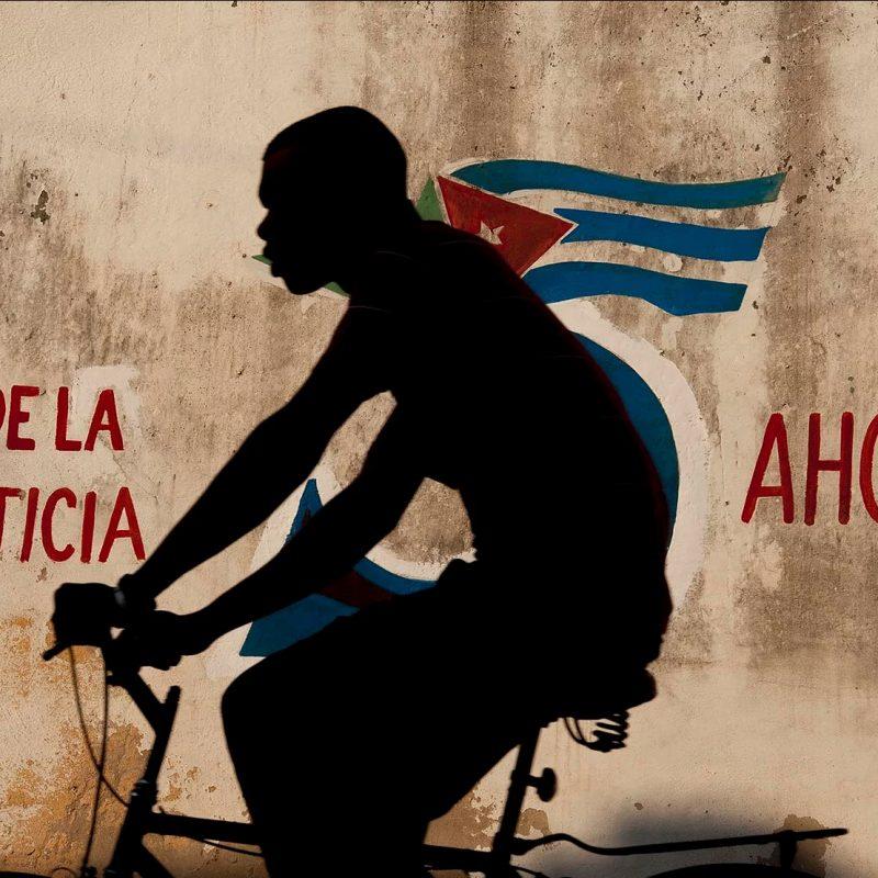 Photo couleur par Alex Almeida, garçon faisant du vélo devant la fresque du drapeau cubain Cuba.