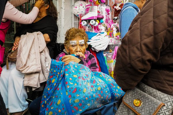 color street photography of an elderly woman by Hakim Boulouiz