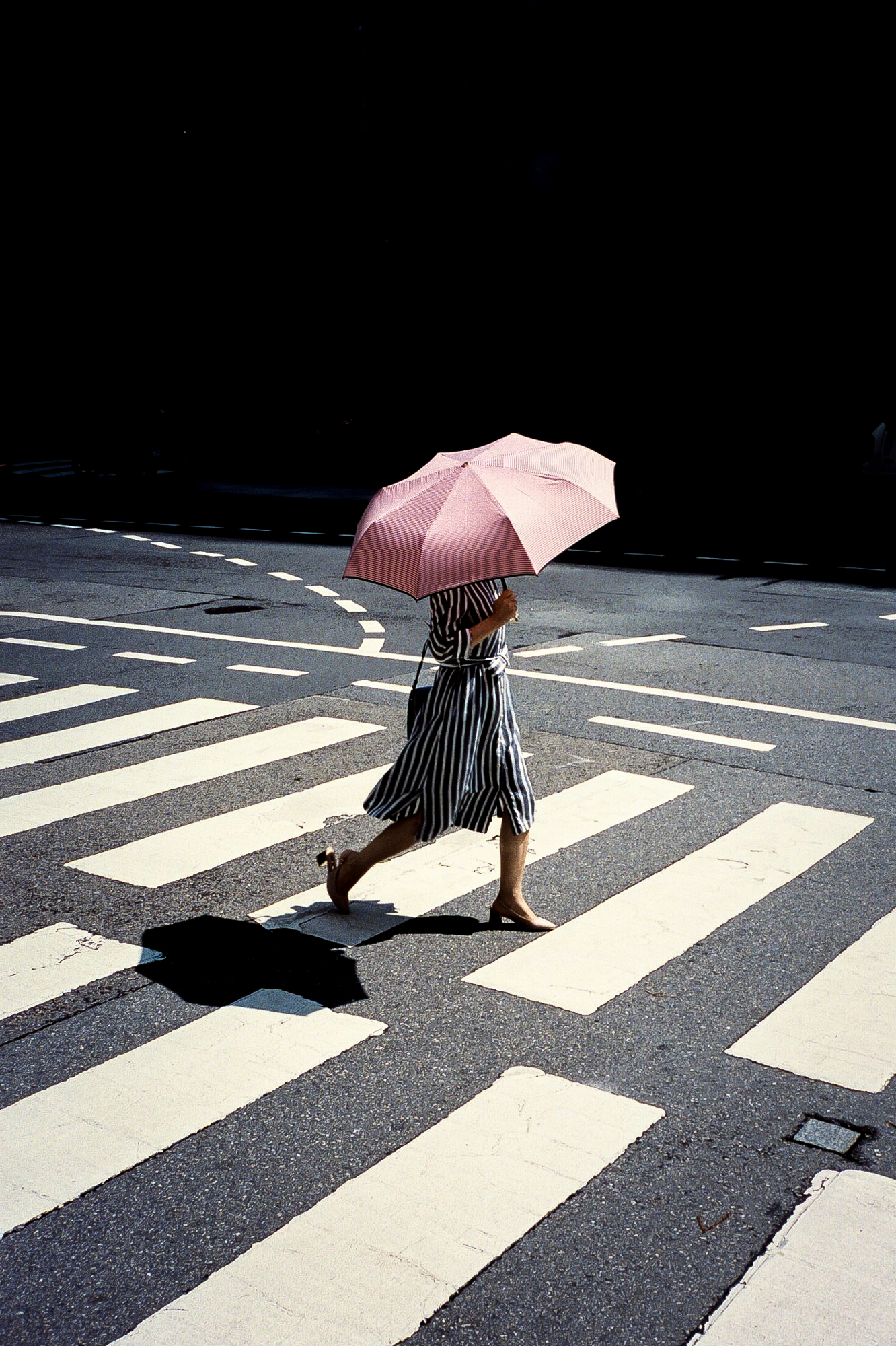 color street photography of a woman crossing the street with pink umbrella by Jim Kostecky