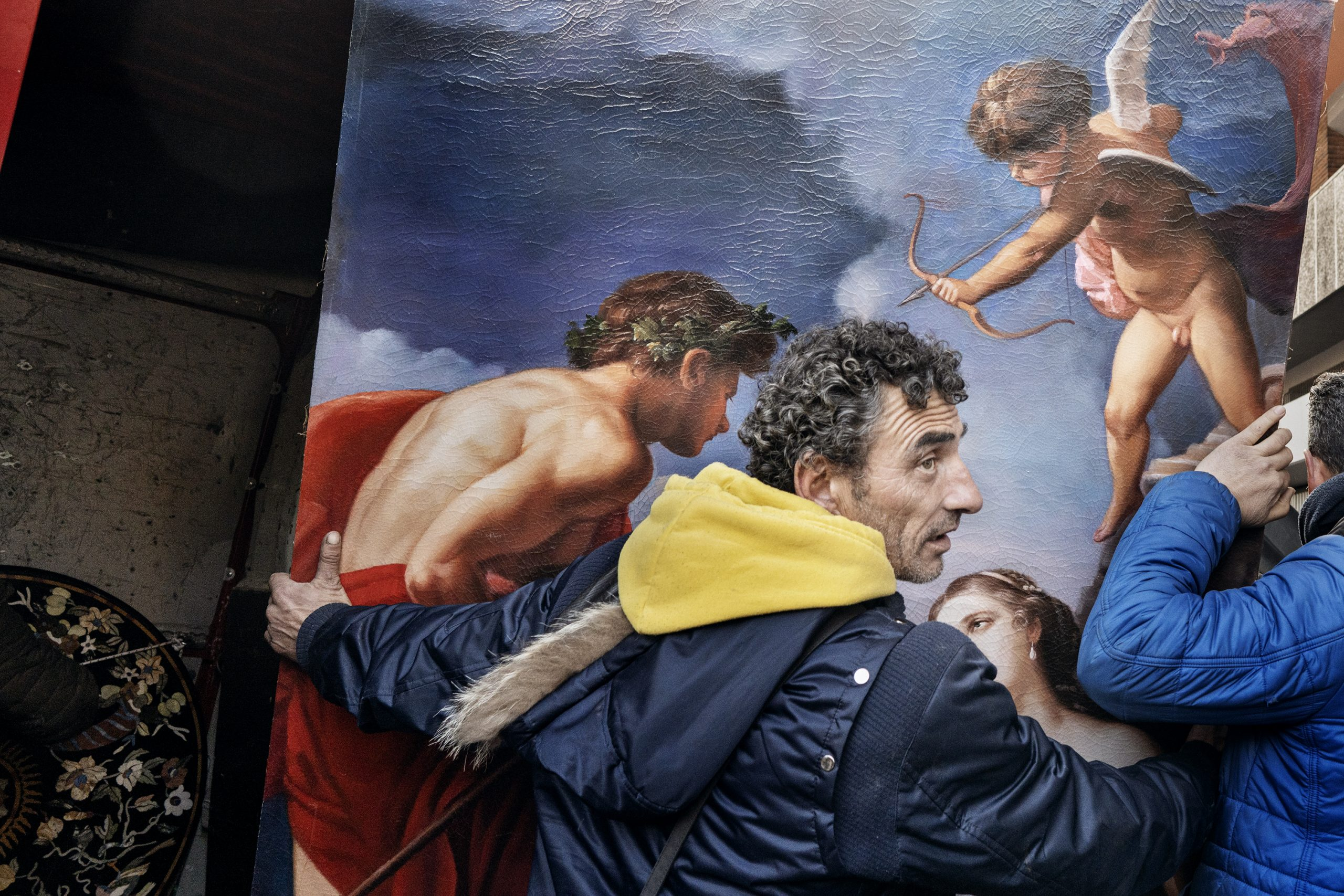 color street photography of a man holding a painting in Rome, Italy by Liliana Ranalletta